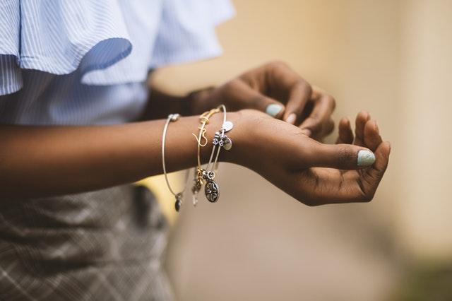 Strieborné a zlaté náramky na ženskom zápästí