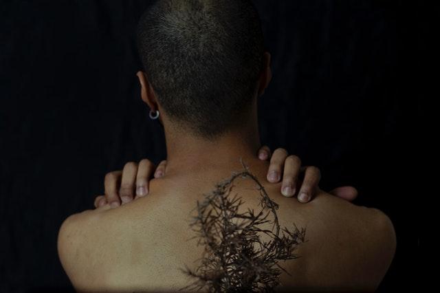 Muž s hnedou pleťou otočený chrbtom sa drží za krk.jpg
